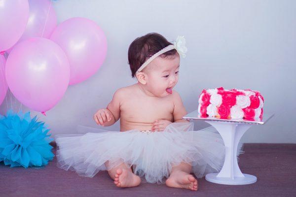 kind in rokje tijdens kinderfeestje op tafel op verjaardagstaart te eten