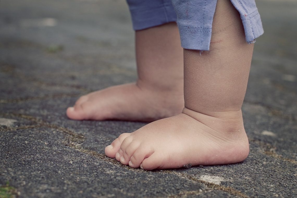 kindervoetjes die staan op een kindvriendelijke vloer