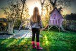 meisje in tuin met fiets en glijbaan